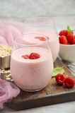 Raspberry and banana smoothie with oatmeal on the rustic wooden table. Selective focus, vertical, copy space Stock Image