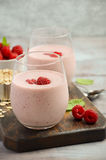 Raspberry and banana smoothie with oatmeal. On the rustic wooden table, selective focus, vertical, copy space Stock Photo