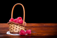 raspberry in basket on wood table Stock Image