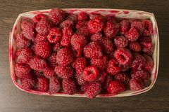 Raspberry in a basket on a wooden background. Raspberries lie in a basket on a wooden background Stock Photos
