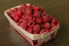 Raspberry in a basket on a wooden background. Raspberries lie in a basket on a wooden background Royalty Free Stock Image