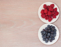 Raspberry and bilberry on the plates. On the wooden background Royalty Free Stock Photos