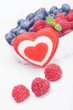 Raspberry bilberry in white bowls and heart. Raspberry and bilberry in white bowls and heart Royalty Free Stock Image