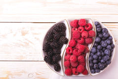 Raspberry, blackberry and blueberry. Healthy food. Top view. Fresh organic ripe raspberry, blackberry and blueberry in ceramic plate on wooden table background Stock Image