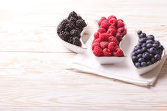 Raspberry, blackberry and blueberry. Healthy food. Top view. Fresh organic ripe raspberry, blackberry and blueberry in ceramic plate on wooden table background Stock Images