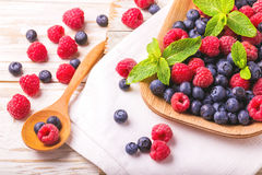 Raspberry, blackberry and blueberry. Healthy food. Top view. Fresh organic ripe raspberry, blackberry and blueberry with mint leaves in ceramic plate on wooden Stock Photography