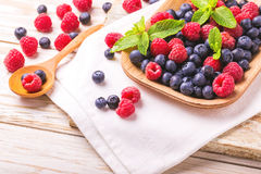 Raspberry, blackberry and blueberry. Healthy food. Top view. Fresh organic ripe raspberry, blackberry and blueberry with mint leaves in ceramic plate on wooden Stock Photo