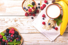 Raspberry, blackberry and blueberry, oatmeal breakfast with milk. Fresh raspberry, blackberry and blueberry with mint in ceramic bowls. Ingredients for oatmeal Royalty Free Stock Image