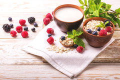 Raspberry, blackberry and blueberry, oatmeal breakfast with milk. Fresh raspberry, blackberry and blueberry with mint in ceramic bowls. Ingredients for oatmeal Stock Images