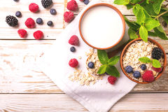 Raspberry, blackberry and blueberry, oatmeal breakfast with milk. Fresh raspberry, blackberry and blueberry with mint in ceramic bowls. Ingredients for oatmeal Stock Image
