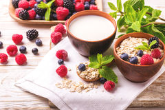 Raspberry, blackberry and blueberry, oatmeal breakfast with milk. Fresh raspberry, blackberry and blueberry with mint in ceramic bowls. Ingredients for oatmeal Stock Photos