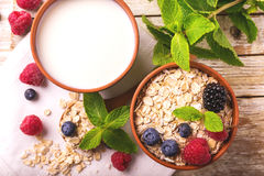 Raspberry, blackberry and blueberry, oatmeal breakfast with milk. Fresh raspberry, blackberry and blueberry with mint in ceramic bowls. Ingredients for oatmeal Stock Photography