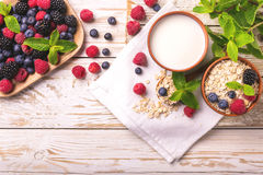 Raspberry, blackberry and blueberry, oatmeal breakfast with milk. Fresh raspberry, blackberry and blueberry with mint in ceramic bowls. Ingredients for oatmeal Royalty Free Stock Photos
