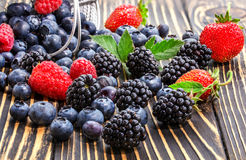 Raspberry, blackberry and blueberry  on a wooden table. Royalty Free Stock Images