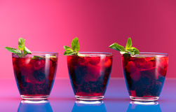 Raspberry and blackberry cocktail with mint garnish. Stock Photos