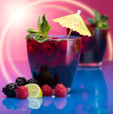 Raspberry and blackberry cocktail with mint garnish. Studio shot, , with sun flare, bokeh stock photography