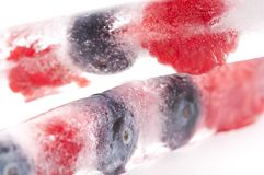 Raspberry and blackberry frozen in ice sticks Royalty Free Stock Images