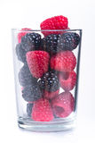 Raspberry and blackberry in glass on white Royalty Free Stock Photo