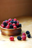 Raspberry and blackberry. Raspberries and blackberries in a wooden plate on a wooden background Royalty Free Stock Photos