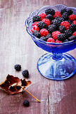 Raspberry and blackberry in a vintage cup. On a wooden plate (selective focus Royalty Free Stock Images