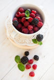 Raspberry and BlackBerry in white plate , selective focus. Raspberry and BlackBerry in white plate on white table, selective focus Stock Photos