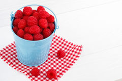 Raspberry. In a blue bucket on white wooden table Stock Images