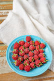 Raspberry in blue dish and in front of white fabric on old vi Royalty Free Stock Images