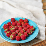 Raspberry in blue dish and in front of white fabric on old vi Stock Image
