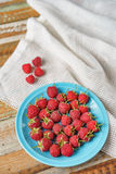 Raspberry in blue dish and in front of white fabric on old vi Royalty Free Stock Photo