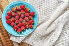 Raspberry in blue dish and in front of white fabric on old vi Royalty Free Stock Image