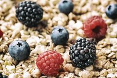 Raspberry, blueberries, blackberries close-up on background of muesli. Healthy breakfast, right lifestyle, detox. Oat flakes, granola, muesli and berries close Royalty Free Stock Photography
