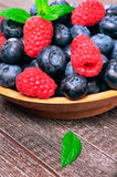 Raspberry and blueberry. Background of raspberry and blueberry with a sprig of mint Stock Photo