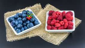 Raspberry and blueberry. Blue and red forest fruit in white bowls on a black background with decorative mat in HD ratio 16x9 royalty free stock photos