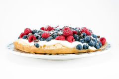 Raspberry and blueberry cake. Side view of a fruit tart with raspberries and blueberries Royalty Free Stock Photography
