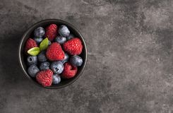 Raspberry and blueberry grey background top view royalty free stock photo