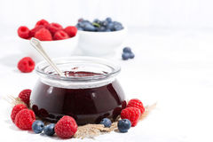 Raspberry and blueberry jam in a glass jar on white background Royalty Free Stock Photos