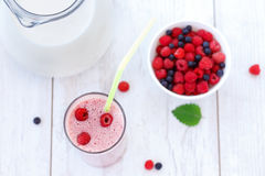 Raspberry and blueberry milkshake on wooden table Stock Photos