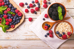 Raspberry, blueberry with mint and oatmeal breakfast or smoothie. Fresh raspberry, blackberry and blueberry with mint leaves in ceramic bowls on wooden table Royalty Free Stock Photo