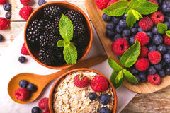 Raspberry, blueberry with mint and oatmeal breakfast or smoothie. Fresh raspberry, blackberry and blueberry with mint leaves in ceramic bowls on wooden table Royalty Free Stock Images