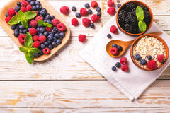 Raspberry, blueberry with mint and oatmeal breakfast or smoothie. Fresh raspberry, blackberry and blueberry with mint leaves in ceramic bowls on wooden table Stock Photo