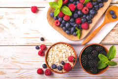 Raspberry, blueberry with mint and oatmeal breakfast or smoothie. Fresh raspberry, blackberry and blueberry with mint leaves in ceramic bowls on wooden table Stock Photos