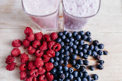 Raspberry and blueberry smoothie with fresh berries on wood tabl. Raspberry and blueberry smoothie milkshakes with many fresh berries on summer wood table Stock Image
