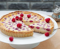 Raspberry, blueberry and white chocolate tart on a white plate Selective focus Royalty Free Stock Image