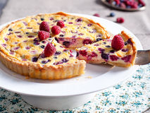 Raspberry, blueberry and white chocolate tart on a white plate Selective focus Royalty Free Stock Photos