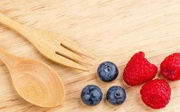 Raspberry and blueberry on wood background, Fresh fruit,. Spoon fork Royalty Free Stock Image
