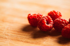 Raspberry on a blurred background of wooden planks.  Stock Images