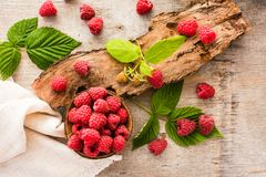 Raspberry in a bowl, berries and leaves on a shabby  wood. Top view Royalty Free Stock Images