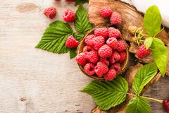 Raspberry in a bowl, berries and leaves on a shabby  wood. Top view Royalty Free Stock Photos