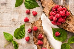 Raspberry in a bowl, berries and leaves on a shabby  wood. Top view Stock Photos