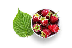 Raspberry in bowl and green leaf. Isolated on white background Royalty Free Stock Images